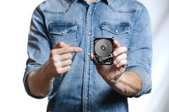La mano del ` s del hombre sostiene 2 disco duro de 5 pulgadas Aislado en el fondo blanco Foto de archivo libre de regalías