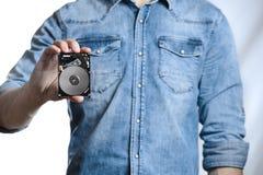 La mano del ` s del hombre sostiene 2 disco duro de 5 pulgadas En el fondo blanco Imagenes de archivo
