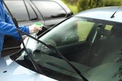 La mano del ` s dell'uomo applica il liquido per pulire il parabrezza della finestra di automobile fotografie stock