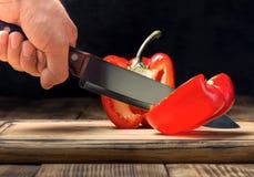 La mano del ` s dell'uomo con un coltello da cucina taglia il peperone Fotografia Stock Libera da Diritti