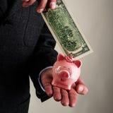 La mano del ` s dell'uomo con una banconota in dollari di carta metterà un porcellino salvadanaio fotografie stock libere da diritti
