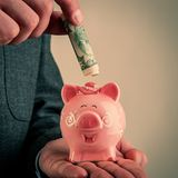 La mano del ` s dell'uomo con una banconota in dollari di carta metterà un porcellino salvadanaio immagine stock libera da diritti