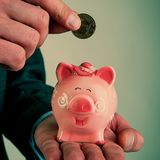 La mano del ` s dell'uomo con una moneta metterà un hryvnia e un porcellino salvadanaio Fotografia Stock Libera da Diritti