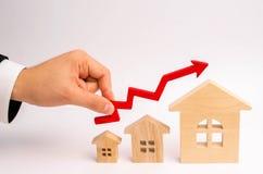 La mano del ` s dell'uomo d'affari tiene la freccia rossa su sopra le case Il concetto di crescita della richiesta del bene immob immagine stock libera da diritti
