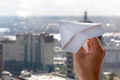 La mano del ` s dell'uomo lancia un aeroplano di carta in una finestra contro lo sfondo della città immagine stock libera da diritti