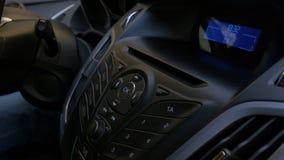 La mano del ` s dell'uomo mette il disco nel giocatore dell'automobile Controllo del bottone per il lettore di compact-disk in un Immagine Stock
