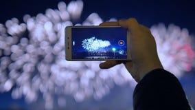 La mano del ` s dell'uomo sta tenendo un telefono e sta registrando un video dei fuochi d'artificio stock footage