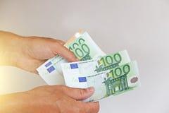 La mano del ` s dell'uomo tiene l'euro 100, li considera e paga Pape Immagine Stock