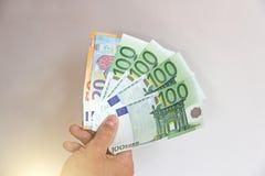 La mano del ` s dell'uomo tiene l'euro 100, li considera e paga Pape Immagini Stock Libere da Diritti