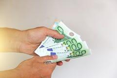 La mano del ` s dell'uomo tiene l'euro 100, li considera e paga Pape Fotografie Stock Libere da Diritti