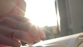 La mano del ` s della donna meravigliosamente gira le pagine del tascabile sul tramonto stock footage