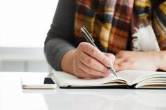 La mano del ` s della donna scrive la a in diario nero immagini stock