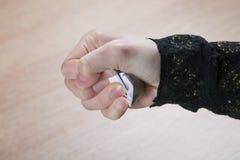 La mano del ` s della donna sgualcisce pezzo di carta Immagine Stock