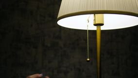 La mano del ` s della donna spegne la lampada stock footage