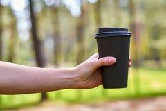 La mano del ` s della ragazza raggiunge per una tazza del caffè di mattina per energia Fotografie Stock Libere da Diritti