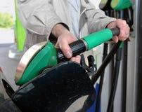 La mano del ` s del hombre con el surtidor de gasolina Imagen de archivo libre de regalías