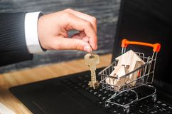 La mano del ` s del hombre de negocios lleva a cabo las llaves cerca de la carretilla con las casas compra e inversión en negocio fotografía de archivo