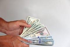 La mano del ` s del hombre lleva a cabo dólares de EE. UU., los cuenta y paga Papel lunes Foto de archivo libre de regalías