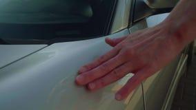 La mano del ` s del hombre resbala en el coche deportivo de plata y abre la puerta del ` s del conductor metrajes