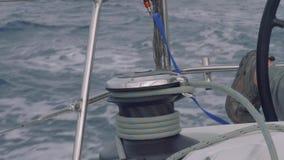 La mano del ` s del hombre saca la manija del torno que se coloca a bordo de la navegación del yate en el océano almacen de video