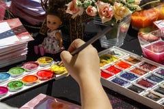 La mano del ` s del niño sostiene una brocha para pintar en el papel en un taller creativo afuera en un día soleado C foto de archivo
