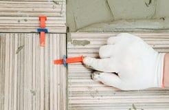La mano del ` s del piastrellista sta allineando le mattonelle Fotografia Stock Libera da Diritti