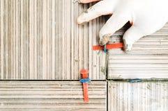 La mano del ` s del piastrellista sta allineando le mattonelle Immagini Stock Libere da Diritti