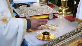 La mano del ` s del sacerdote batezza una tazza di vino stock footage