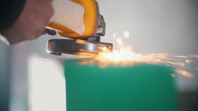 La mano del ` s del trabajador está moliendo el mecanismo de acero en la industria, a cámara lenta metrajes
