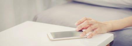 La mano del sito Web dell'insegna del primo piano della donna spegne l'allarme sul telefono cellulare di chiamata mentre svegli d fotografia stock libera da diritti