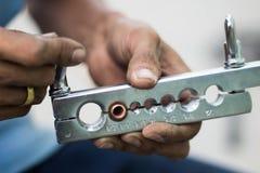 La mano del tecnico con lo strumento scintillante del tubo nel servizio di stato dell'aria Immagine Stock