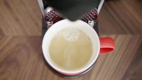 La mano del tipo elimina la tazza rossa con caffè dal vassoio di macchina automatica del caffè archivi video