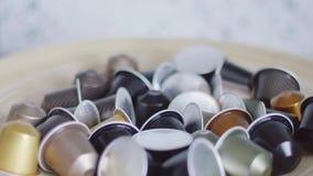 La mano del tipo prende la capsula del caffè nero dalla ciotola con i lotti di altre capsule archivi video