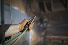 La mano del trabajador de construcción del acceso de la cuerda que sostiene deadman de funcionamiento de la chorreadora de arena  fotografía de archivo
