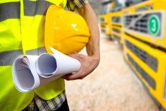 la mano del trabajador de construcción que sostiene documentos y el casco del proyecto Foto de archivo libre de regalías