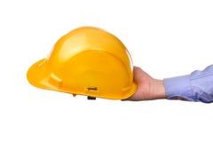 La mano del trabajador de sexo masculino que sostiene el casco protector industrial amarillo Fotografía de archivo