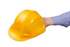 La mano del trabajador de sexo masculino que sostiene el casco protector industrial amarillo Foto de archivo