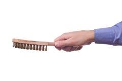 La mano del trabajador de sexo masculino que sostiene el cepillo de los bristes del alambre de acero Foto de archivo libre de regalías