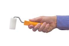 La mano del trabajador de sexo masculino que sostiene el rodillo de pintura Imágenes de archivo libres de regalías