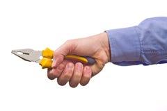 La mano del trabajador de sexo masculino que sostiene los alicates de la combinación Foto de archivo libre de regalías