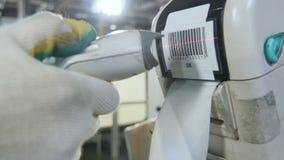 La mano del trabajador del primer explora la etiqueta engomada del código de barras en la impresora en taller