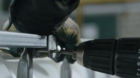 La mano del trabajador tuerce el tornillo en marco acabado del envase almacen de metraje de vídeo