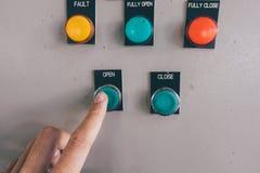 La mano del uso es ajusta el interruptor en el gabinete de control eléctrico Foto de archivo libre de regalías