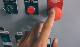 La mano del uso es botón de la emergencia del empuje en el gabinete de control eléctrico Fotografía de archivo