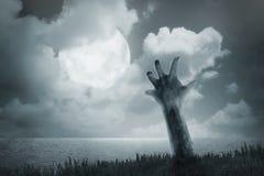 La mano del zombi sale de la tierra Imágenes de archivo libres de regalías