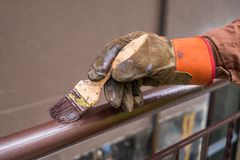 La mano dell'appaltatore con la spazzola che costruzione di rotaia del metallo della pittura immagini stock libere da diritti