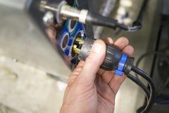 La mano dell'elettricista inserisce la spina nell'incavo Immagini Stock