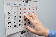 La mano dell'impiegato di concetto indica le feste di maggio su uno strato del calendario murale fotografia stock