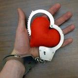 La mano dell'uomo è ammanettata, tenendo un cuore molle rosso su un fondo marrone Un'immagine quadrata Il concetto di amore e del immagine stock