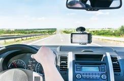La mano dell'uomo è sul volante ed i gps è sui venti Fotografia Stock